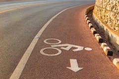 骑自行车与自行车路标的车道在沥青车道 库存照片