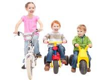 骑自行车乘坐trikes的儿童孩子 免版税库存照片