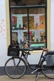 骑自行车儿童` s服装店Prinses en窗口的前面  免版税库存照片
