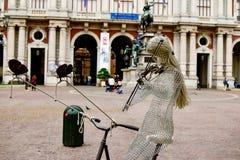 骑自行车和在其中一个的妇女的美好的雕塑弹小提琴最著名的正方形中在城市 免版税库存照片