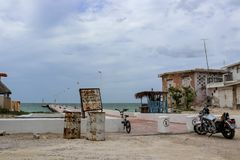骑自行车和在码头和老饱经风霜的房子附近停放的摩托车在Progesso尤加坦墨西哥附近7 - 06 - 2017年 免版税库存照片