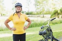 骑自行车和放松在乡下的活跃资深妇女在明亮的阳光下 库存照片