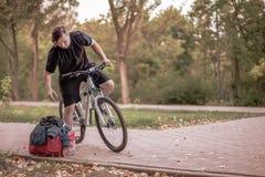 骑自行车在公园的年轻白种人人 免版税库存照片