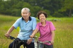 骑自行车在公园的愉快的亚洲前辈夫妇 免版税库存图片