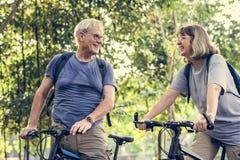 骑自行车在公园的资深夫妇 免版税库存图片