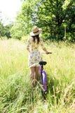 骑自行车在夏天公园的愉快的相当女孩 愉快在城市放松时间 美丽的妇女,晴天 免版税图库摄影