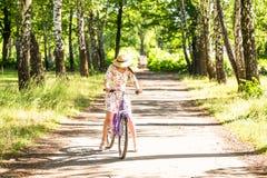 骑自行车在夏天公园的愉快的相当女孩 愉快在城市放松时间 美丽的妇女,晴天 免版税库存照片