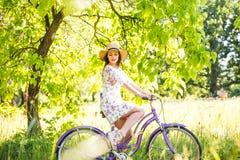 骑自行车在夏天公园的愉快的相当女孩 愉快在城市放松时间 美丽的妇女,晴天 库存图片
