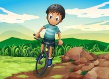 骑自行车在小山顶的孩子 图库摄影