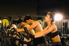 骑自行车在户内与行使的健身房的小组三个人 库存照片