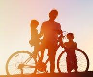 骑自行车在日落的父亲和两个孩子剪影  库存图片