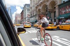 骑自行车在曼哈顿交通的少妇 图库摄影