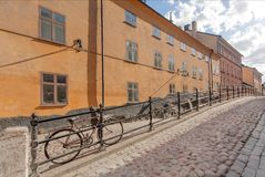 骑自行车在有被修补的石头的街道上,停放在五颜六色的历史房子之间 斯德哥尔摩,瑞典老地区  库存照片