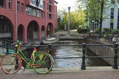 骑自行车在有运河的在背景中-阿姆斯特丹,荷兰一座桥梁 库存图片