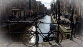 骑自行车在桥梁在阿姆斯特丹有运河背景 免版税库存图片