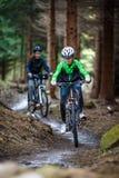 骑自行车在森林的十几岁的女孩和男孩落后 库存照片