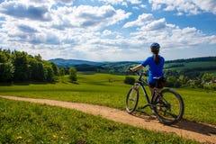 骑自行车在森林足迹的十几岁的女孩 库存照片