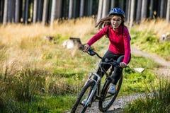 骑自行车在森林足迹的十几岁的女孩 免版税库存照片