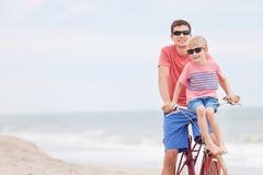 骑自行车在海滩的家庭 免版税库存图片