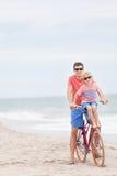 骑自行车在海滩的家庭 免版税库存照片
