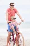 骑自行车在海滩的家庭 库存照片