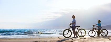 骑自行车在海滩的母亲和儿子 库存照片