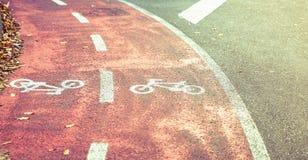 骑自行车在自行车车道的路标志与秋天 免版税库存图片