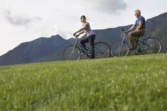 骑自行车在草的夫妇反对山脉 免版税库存照片