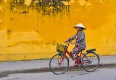 骑自行车在街道上的一个老妇人在越南 免版税库存图片