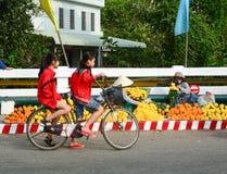 骑自行车在街道上的人们在芹苴市,越南南方 免版税库存图片