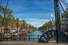 骑自行车在运河有老大厦的和蓝天的开启桥在阿姆斯特丹 库存图片