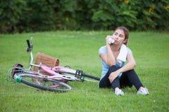 骑自行车在骑马妇女年轻人之外的愉快的健康生活方式 免版税库存照片