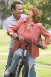 骑自行车夫妇成熟骑马 库存图片