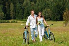 骑自行车夫妇草甸浪漫夏天 免版税库存照片