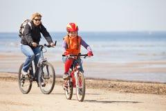 骑自行车女儿母亲骑马 免版税库存照片