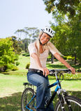 骑自行车她的公园妇女 免版税库存图片