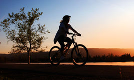 骑自行车她的骑马妇女 免版税图库摄影