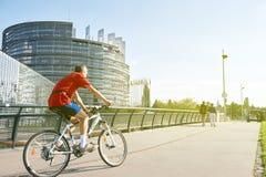 骑自行车嬉戏史特拉斯堡,欧洲议会修造的老人 免版税库存图片