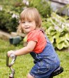 骑自行车小的女孩 免版税库存照片