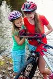 骑自行车循环的女孩 儿童乘驾自行车 自行车骑士手表片剂计算机 免版税库存图片
