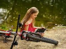 骑自行车循环的女孩 女孩有休息在自行车附近入公园 库存图片