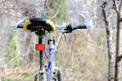 骑自行车有红色反射器的马鞍,蓝色自行车,室外 免版税库存图片
