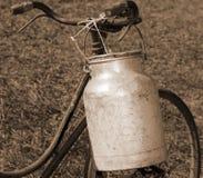 骑自行车有铝容器的送牛奶者运输的牛奶从 免版税库存照片