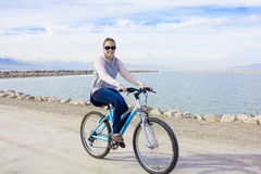 骑自行车沿江边的健康妇女 图库摄影