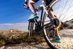 骑自行车浅骑自行车的骑自行车者深度域重点森林现有量山的透视图 体育和健康生活 免版税库存照片