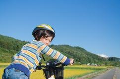骑自行车男孩骑马 免版税库存图片