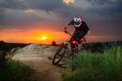 骑自行车的专业骑自行车者在山岩石足迹在日落 极其体育运动 免版税库存照片
