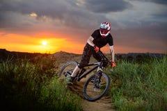 骑自行车的专业骑自行车者在山岩石足迹在日落 极其体育运动 库存照片