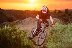 骑自行车的专业骑自行车者在山岩石足迹在日落 极其体育运动 免版税图库摄影