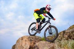骑自行车的专业骑自行车者在岩石的上面 极端体育概念 文本的空间 免版税图库摄影